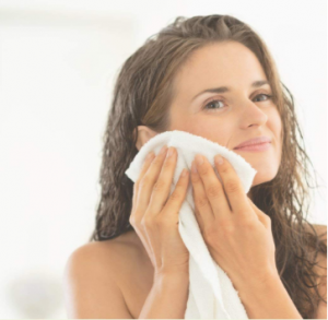 Women with wet hair patting her face dry with a white towel